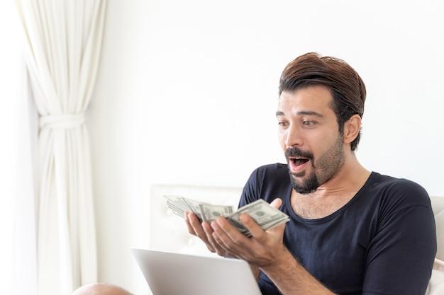 Деловой человек держит деньги долларовые купюры в домашнем офисе Бесплатные Фотографии