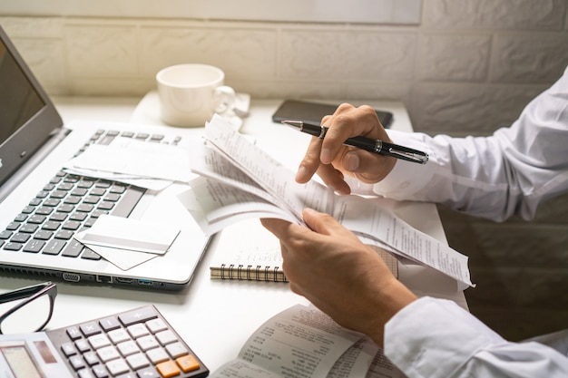 A business man holding pen while looking at the bills in his workplace. business concept. Premium Photo