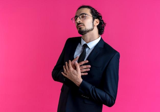ピンクの壁の上に立っていることに感謝を感じて脇を見て胸に手を渡った黒いスーツと眼鏡のビジネスマン 無料写真