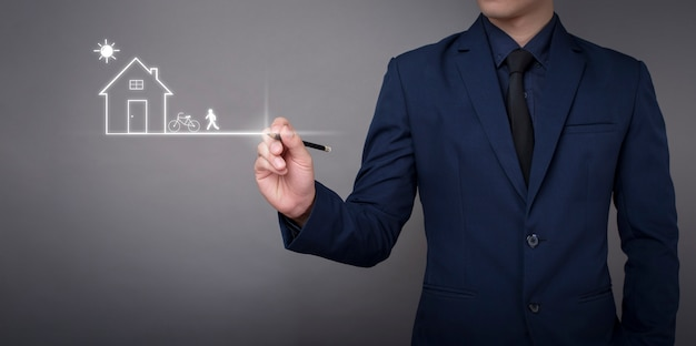 Business man is drawing the home on digital virtual screen Premium Photo