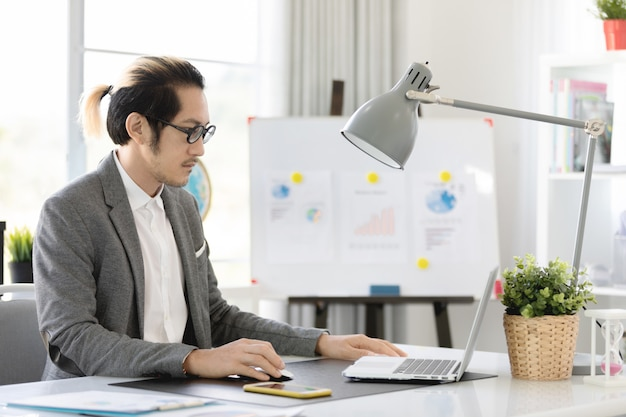 Business man in office  using laptop and cell phone, Premium Photo