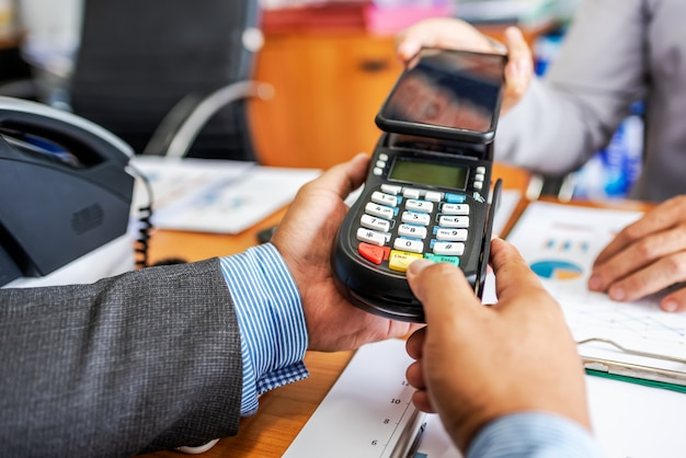 Business man payment by nfc technology with credit card reader machine and smartphone app. Premium Photo