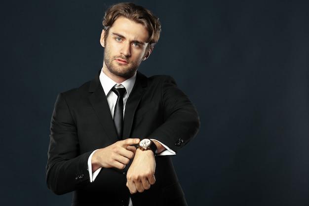 Деловой человек, указывая на свои часы Premium Фотографии