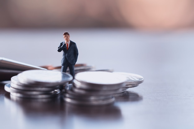 Business man,saving,investment and finance concepts. miniature people stand Premium Photo