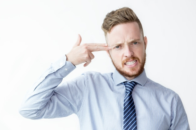 Business man shooting himself with fingers Free Photo