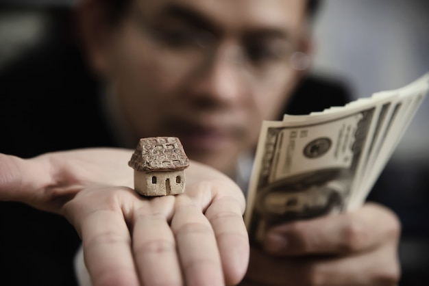 Business man show money bank note make financial plan invite people to sell or buy house and car - monetary properties loan credit insurance concept Free Photo