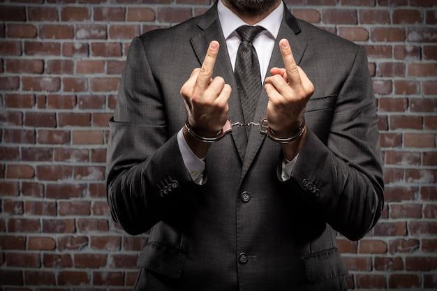 刑務所に手錠で彼の中指を見せびらかしているビジネスマン。腐敗、腐敗した政治家、違法ビジネスの概念。レンガの背景。 Premium写真