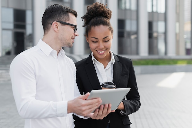 Business man showing ipad to woman Free Photo