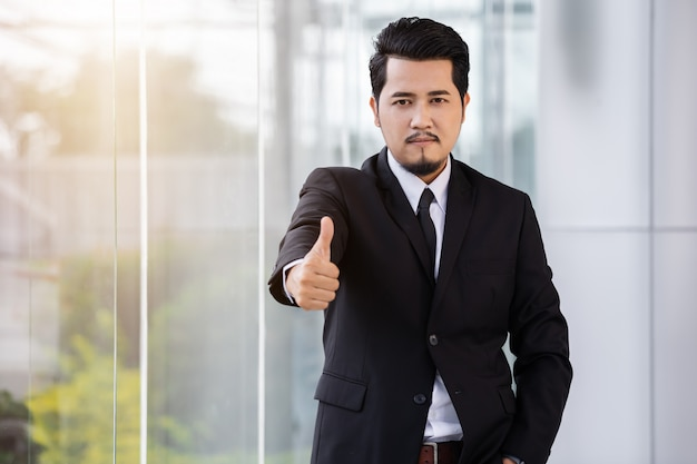 Business man showing thumbs up sign in office Premium Photo