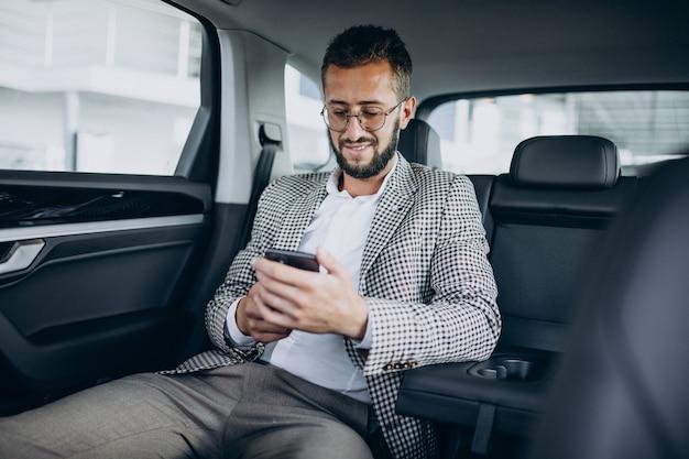 Uomo d'affari seduto sul sedile posteriore di un'auto utilizzando tablet Foto Gratuite
