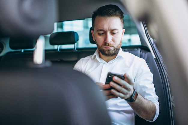 Business man sitting in a car using phone Free Photo