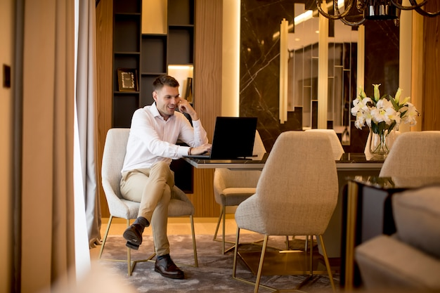 Business man sitting in a luxurious room in front of a laptop Premium Photo