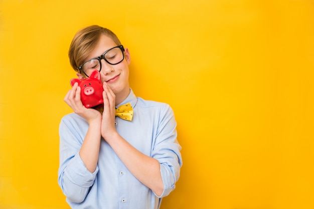 Business man. smiling teenage boy holding a red piggy bank. business concept. saving money concept. bank advertising. piggybank. finance Premium Photo