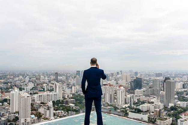 Business man talking on a phone with a cityscape background Premium Photo