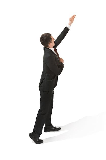 Uomo d'affari, cercando di raggiungere qualcosa su bianco Foto Gratuite