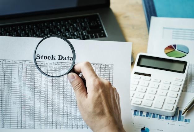 Business man using magnifying to review balance sheet Premium Photo