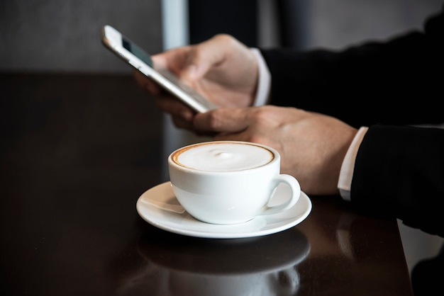 Business man using mobile phone while drinking coffee in coffee shop Free Photo