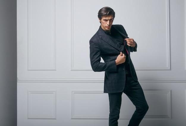 Business man wear black elegant suit portrait against a neoclasic wall. closeup portrait of a hands