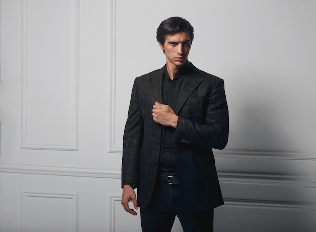 Business man wear black suit portrait against a dark background, looking at the side. closeup portr