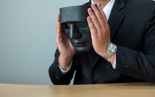 Business man with a black mask covering the insincerity of doing business together. Premium Photo