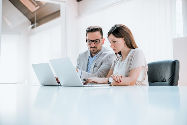 Business man and woman colleagues sitting with laptops on desk in office Premium Photo