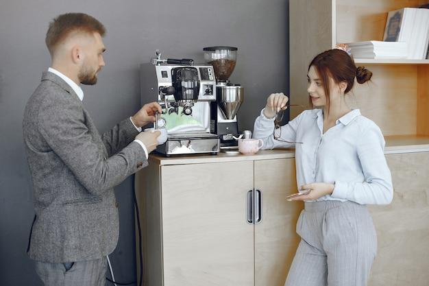 Uomo d'affari e donna in ufficio. pausa caffè nel corridoio della grande azienda. Foto Gratuite