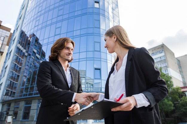 Business man and woman shaking hands Free Photo