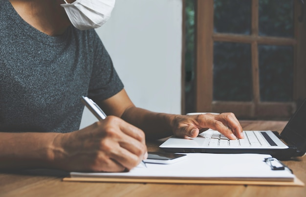 Business man working with computer laptop on wooden table at home. working online business concept. Premium Photo