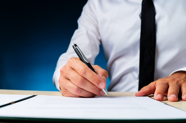 Business manager signing a document in a folder on his desk. over dark blue background. Premium Photo