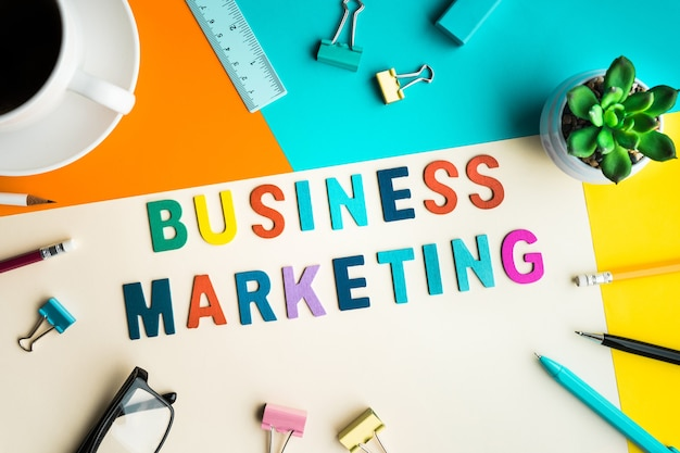 Слово бизнес-маркетинга на столе в офисе с принадлежностями Premium Фотографии