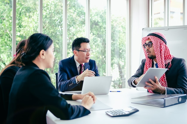 Business meeting asian team and arabic man presenting his ideas in office room Premium Photo
