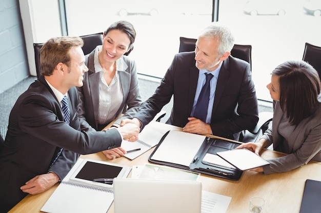 Business men shaking hands in conference room Premium Photo