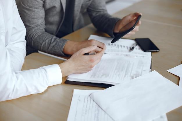 Деловые люди сидят за столом адвоката. люди подписывают важные документы. Бесплатные Фотографии