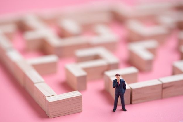 Business miniature at the start point of puzzle maze wood block Premium Photo
