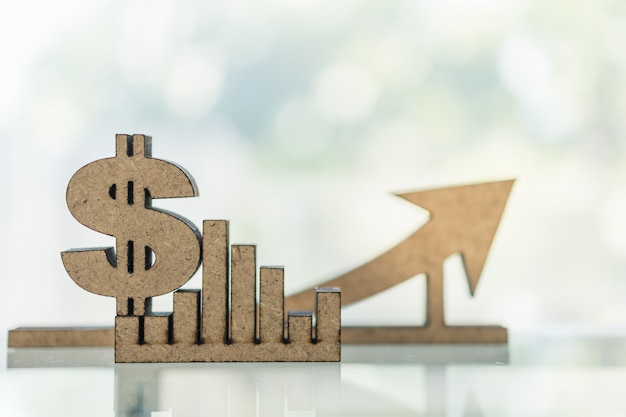 Business, money, finance growth and planning concept. close up of wooden dollar sign and bar chart graph and arrow with copy space. Premium Photo
