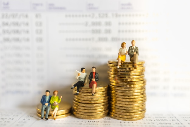 Business, money, financial, secure and saving concept. group of businessman and woman miniature figure people sitting and talking meeting on stack of gold coins on bank passbook. Premium Photo