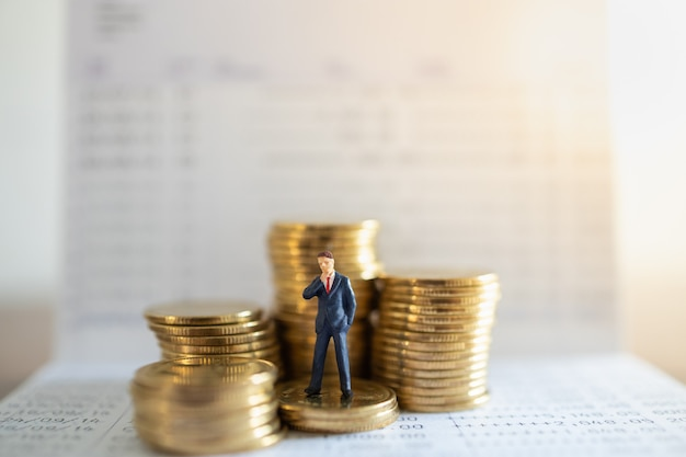 Business, money investment and planning concept.businessman miniature figure people figure standing on stack of gold coins with bank passbook. Premium Photo