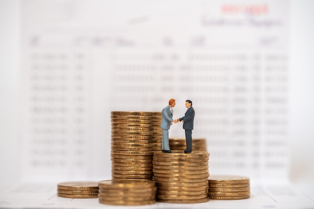 Business money saving and work concept. two businessman miniature figure people stabding and make hand shake on stack of gold coins on bank passbook. Premium Photo