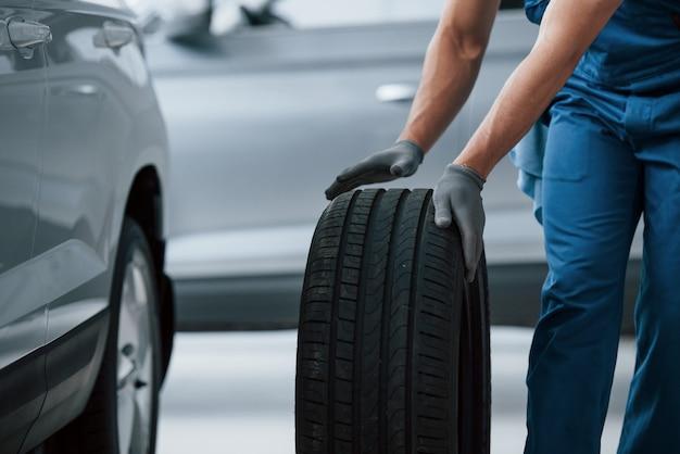 車の修理事業。修理ガレージでタイヤを保持しているメカニック。冬用および夏用タイヤの交換 無料写真