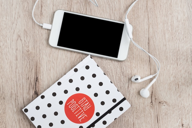 Business and office concept - polka dot cover notebook, smartphone and headphones on wooden table. minimal flat lay, top view. Premium Photo