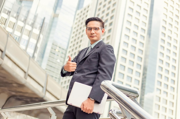 Business and office concept . young asia handsome buisnessman showing thumbs up. Premium Photo
