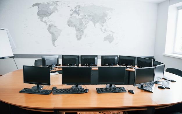 Ufficio commerciale durante il giorno con molti schermi di computer. mappa sul muro Foto Gratuite