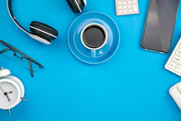 スマートフォンヘッドフォン目覚まし時計とコーヒーカップのビジネスオブジェクトとビジネスオフィスのテーブル。 Premium写真