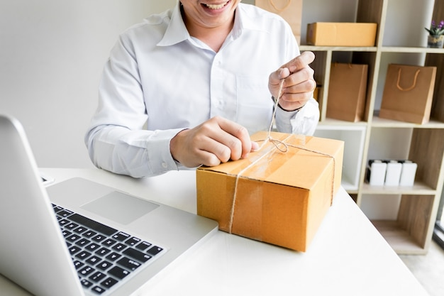 Business owner man working online shopping prepare product packaging process at his home, young entrepreneur concept. Premium Photo