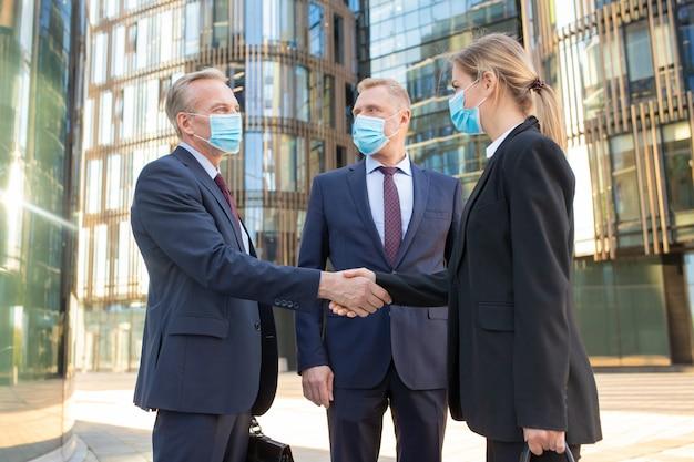Partner commerciali in maschere per il viso che agitano le mani vicino a edifici per uffici, riunioni e parlare in città. vista laterale, angolo basso. comunicazione e concetto di coronavirus Foto Gratuite