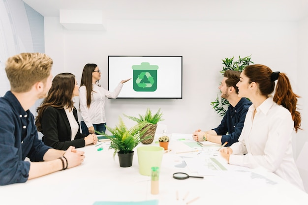 Business partners looking at female manager giving presentation with recycle icon on screen Free Photo