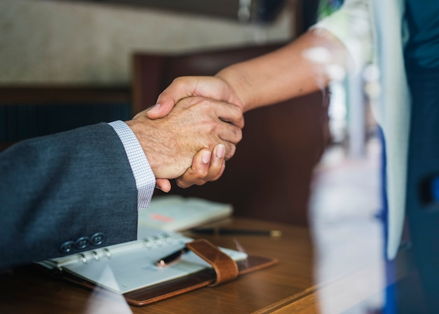 Business partners shaking hands in agreement Free Photo