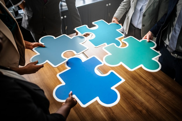 Business people connecting puzzle pieces Free Photo