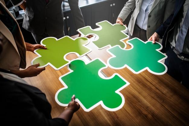 Gente di affari che collega i pezzi del puzzle Foto Gratuite