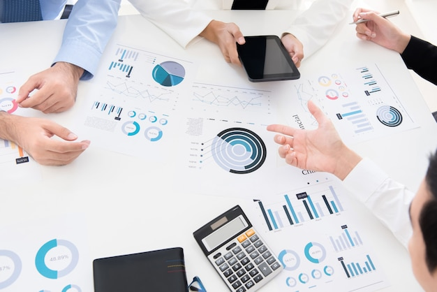 Business people discussing and analyzing financial graph documents Premium Photo